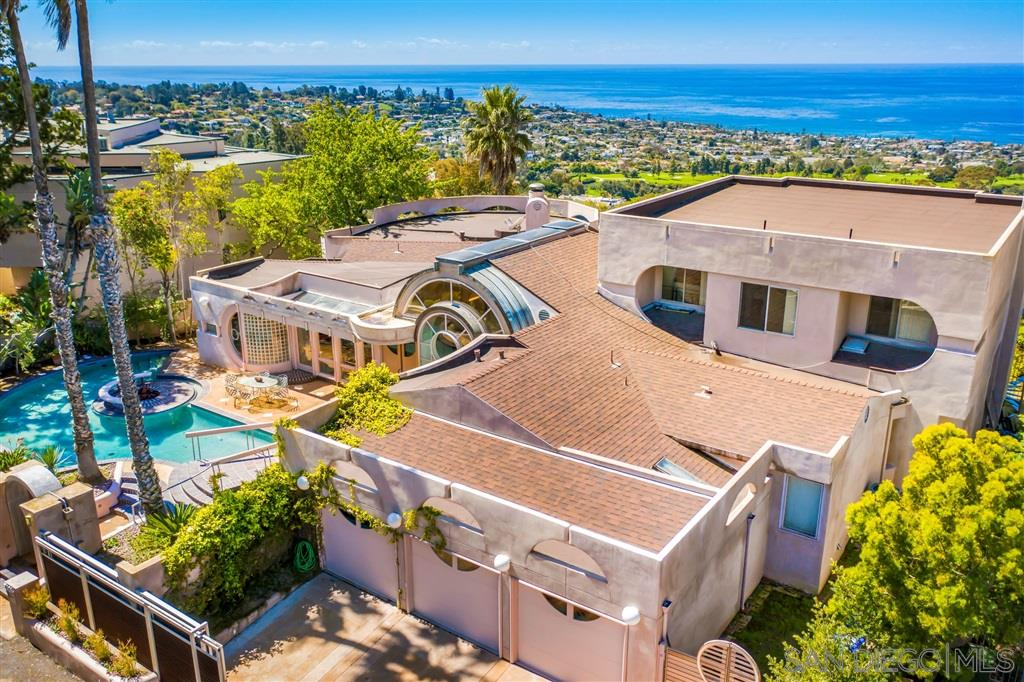 The Sundial, as this home is known, represents the perfect marriage of form and function and is located in the prestigious Country Club area of La Jolla.  It is an architectural gem.  The panoramic ocean and sunset views are ever changing and the entertaining possibilities in this home are magical for small as well as large groups. Circulate freely among the public rooms or make your way outside to the pool surround or ocean view deck. See Supp.The home was built for personal use by internationally renowned architect C.W. Kim, who is responsible for many of the striking features of San Diego's downtown skyline.  This home possesses equal amounts of craftsmanship, elegance and romance.  Of particular note are the dramatic curved wooden ceilings which dominate the grand foyer and lead to the striking living room.  There is a state of the art circular gourmet kitchen with Viking, Miele, and Gaggenau appliances, a grand piano shaped granite island, multiple dishwashers, interchangeable cooktops, grill, exotic lacy wood cabinetry.  Adjacent to the kitchen is the formal dining room which could easily seat twenty guests.  There is a large master suite with two spacious walk in closets, a full marble bathroom with spa tub, a granite fireplace (there is another stunning fireplace in the living room) and of course that incomparable ocean view.  A highlight of the house is the pool with fire pit, and fountain, all accessible by bridge from the gated front entry.  Other rooms of note include the library, and family room.  In addition to the three car garage, there is a 1000 bottle wine cellar, plenty of storage, a sauna, and maids quarters separate from the rest of the house.  A recent addition is the 1000 square foot second story design studio  which could easily become an alternative private master suite with breathtaking views or two additional bedrooms.  Seeing is believing.  We are certain that you will recognize and appreciate the extraordinary detailing of this unique house.  We invite you to consider this one of a kind home.