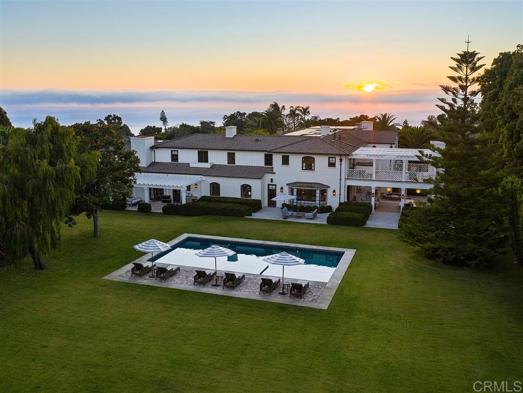 Built in 2013 to the highest of standards, this absolutely amazing home is timeless in its quality, design and location, such that it will remain one of the finest estates in La Jolla for generations to come, providing immeasurable pleasure, comfort and inspiration to anyone fortunate enough to call it home.  Situated privately yet able to capture excellent ocean views, the home was thoughtfully constructed on 2 of 3 parcels that comprise the almost 1.4 acres of land.Fully gated and surrounded by gorgeous landscaping and mature hedges, this California Traditional style home is barely visible from the street. Its 2 above grade levels are exquisite, featuring 6 bedroom suites including separable guest quarters above a 2 car garage, and a main level optional master. Upstairs, the impressive primary master bedroom suite has sitting areas, a fireplace, large shower, his and hers closets and toilets, as well as a large private balcony with a therapeutic spa and fireplace. Elegant, large and chic living, dining and family rooms by acclaimed designer Jeffrey Billhuber facilitate excellent flow for both warm day-to-day living as well as lively entertaining. There are home offices located off of both the kitchen and master. Many rooms flow seamlessly inside to out through pocketing screen doors. A covered patio off of the family room affords the quintessential indoor/outdoor living, dining and entertainment for which La Jolla is loved. Below grade is a wine cellar, theater room with bar, a great deal of storage and an 18+ car showroom, which could also be used in many other ways, such as a bowling alley, gym, recording studio, shooting range, among many other flexible uses. The extensive grounds that include a large UV pool with underwater speakers, ample lawn and garden designed by Art Luna could also accommodate a pool house, sport court and/or be re-partitioned and developed or sold, and a new home built on the annexed lot would have ocean views from its second story as we
