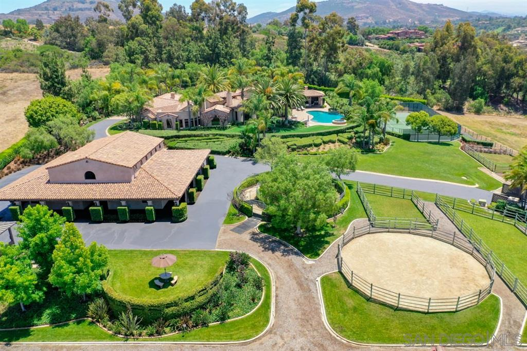 Enjoy This Dream Lifestyle! Immaculate equestrian estate with quality custom home includes 7,400 sf under roof, outdoor dining and entertaining areas, attached guest house, infinity edge pool and tennis court. Gorgeous 9 stall barn with every equine amenity plus office, 1 bedroom apartment and a total of 2 1/2 baths. Huge arena, grass derby field, pastures, euro-walker, on-site trail plus access to miles of trails. Extremely private location with panoramic views over Bridges golf course. Must see!Property includes owned solar, which runs the entire property. Equestrian improvements are truly exceptional, designed for world class show jumping with a lovely barn including full living quarters. Ride on dedicated Encinitas trails for 30 miles and beyond. Location is extremely private and quiet yet is close to restaurants, retail and beaches, with cool, coastal breezes.