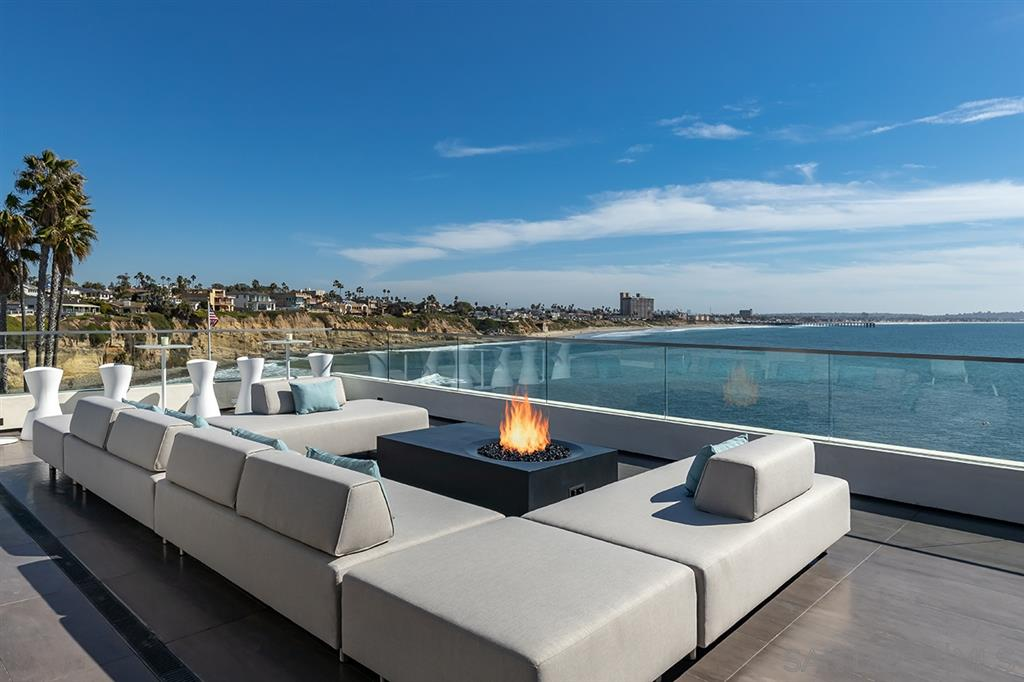 Incomparable ocean views seamlessly integrate with a NEW contemporary masterpiece. La Jolla's Bird Rock Waterfront is now home to an awe-inspiring Blue Heron property that stirs emotions in ways you've never experienced. Perfectly sited and designed to capture unmatched southern and western views, the home offers a floating bridge, cascading water walls, glass foyer, and automated doors that perfectly blend & connect more than 3,000 SF of outdoor living spaces with a world-class, fully-furnished interior.Blue Heron, a nationally recognized and award-winning visionary and experiential firm, has designed and developed its first unmatched custom home in La Jolla. The more than 6,800 SF contemporary and sustainable home provides a unique setting with a view looking south to Crystal Pier, Point Loma, and the Coronado Islands and west to the sunset. 3eleven provides an unmatched modern living experience with a design that has maximized utilization of the lot and vertical space. The home is moved to the side of the lot to offer a long-entry experience over a floating bridge that pulls you toward the ocean view, led by fire and a lap pool spilling down two water walls into multiple vertical voids over the lower living area and entering an all glass foyer where the beach pebbles flow inside to dissolve indoor/outdoor boundaries. The master suite has been purposely laid out wide to maximize the sublime views with glass at the vanity and beyond the bed wall to allow for ocean views from every angle- from the bathroom to the oversized master closet and outdoor shower. A roof top entertainment space boasts magnificent 270-degree ocean views with a spa, adjacent bar, outdoor cooking, and a covered space shaded by a trellis of solar panels with strategically placed outdoor TVs. Other intentional spaces include three additional bedrooms and baths, two powder rooms, and media, wine and game rooms. An elevator and three-story stairwell provide access to multiple levels of contemporar