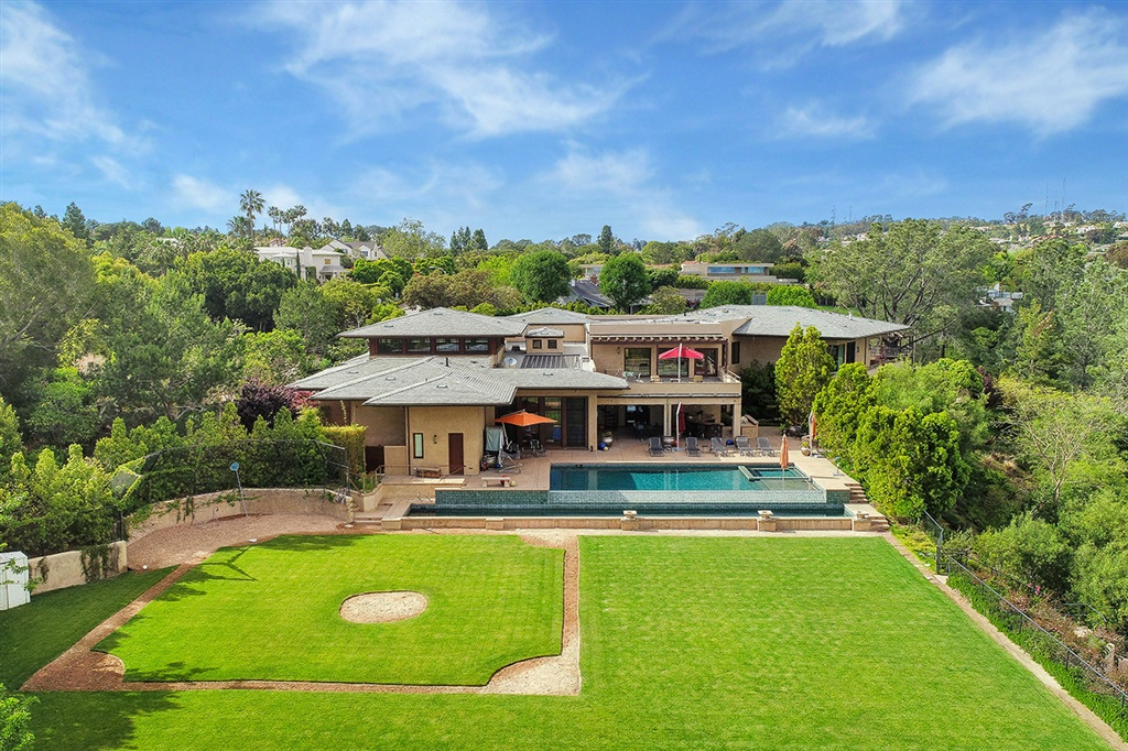 This extraordinary, zen-inspired architectural home is a hidden oasis in one of San Diego's most prestigious enclaves, La Jolla. Set on over 3 ½ acres, the home features gorgeous Japanese gardens, breathtaking city views and a sleek, contemporary aesthetic replete with chef's kitchen, tiered cinema, fitness center, yoga studio and exceptional master suite. Resort-caliber amenities include two pools, a loggia with a bar and grill, grassy baseball field, tennis and basketball courts.This extraordinary, zen-inspired architectural home is a hidden oasis in La Jolla - one of San Diego's most prestigious enclaves. Showcasing more than three-and-a-half acres of lush, landscaped grounds, resort-caliber amenities and breathtaking city views, the home embodies the quintessential Southern California lifestyle with an air of the exotic.  Set behind handcrafted gates, a private drive surrounded by mature trees leads to this secret hideaway, with beautifully landscaped gardens and meandering pathways rife with palms and bonsai providing an ethereal moment at every turn. A Japanese footbridge over a storybook-like creek leads to the 13,532-square-foot stunner, which features a sleek, contemporary aesthetic enriched with exotic woods, soaring, decorative ceilings and sophisticated finishes. Highlights include a chef's kitchen with high-end appliances and eat-in island, elegant dining room overlooking lush gardens, parlor with a bar and tiered cinema with built-in theater seating. Sliding pocket doors off the spacious great room fuse the interiors with an exceptional outdoor entertainment center, complete with a dining loggia and horseshoe-shaped bar with a built-in grill. Six ensuite bedrooms are voluminous and bright, including the exceptional master suite with a spa-like bathroom, staggering showroom closet, distinctive fireplace, private balcony and window walls framing lush greenery. A fitness center and yoga studio feature an expansive terrace overlooking the home's magnificent grounds.  Exquisitely conceived for year-round recreation and entertaining, a vast backyard boasts a resort-like pool and spa that spill into a lower-level lap pool, sprawling, grassy baseball field, tennis and basketball courts. At once a showpiece of unbridled design and a refuge of peace and serenity, this magnificent retreat is mere minutes from the beach, La Jolla Village and the heart of San Diego.