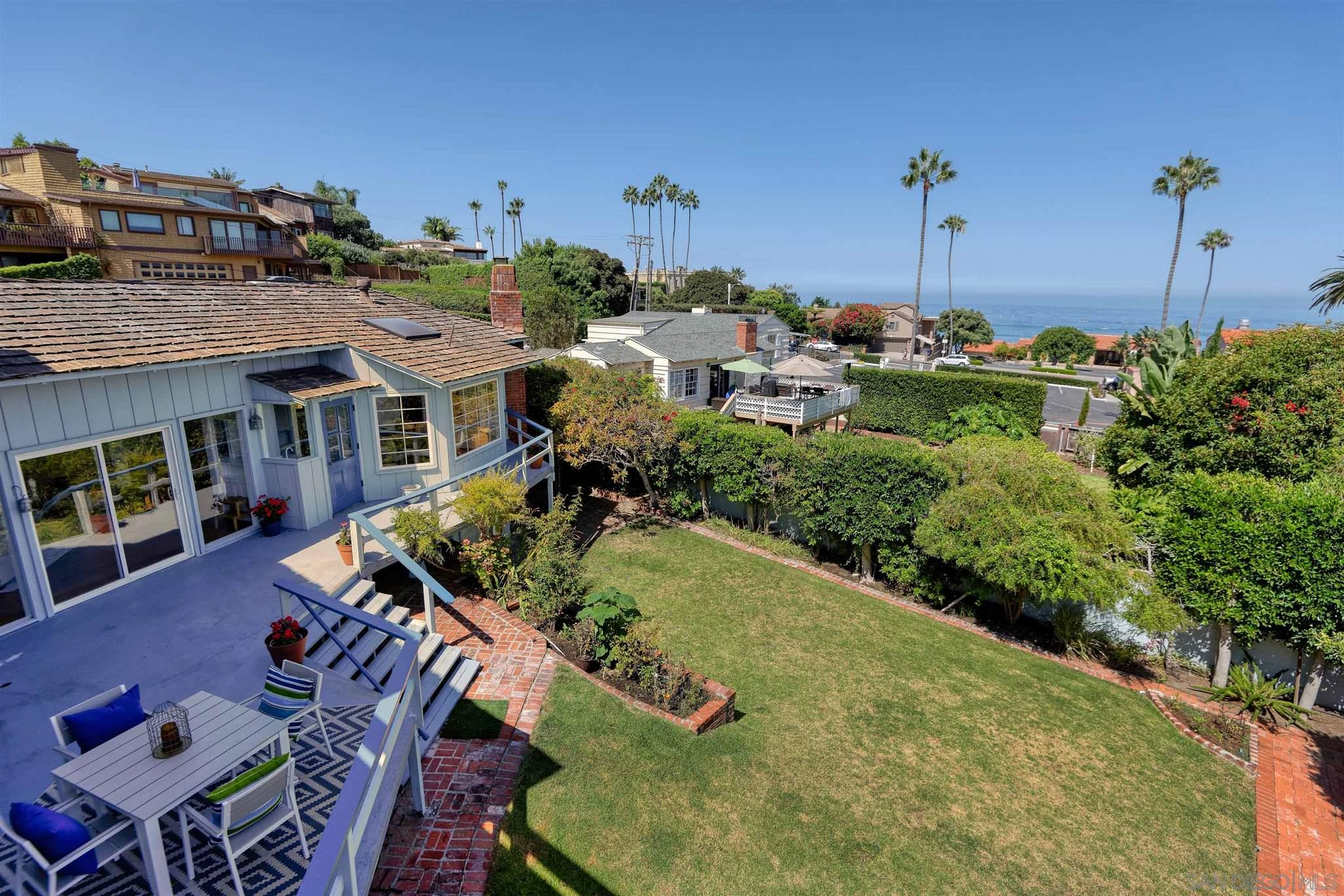 With ocean views in a superb La Jolla Shores location above La Jolla Beach & Tennis Club, this classic traditional home offers a welcoming gated courtyard entrance, bright, broad windows, doors, and skylights bringing in  wonderful natural sunlight with views to open sea, the picturesque, rugged cliffs of the North Shore, and the lush canopy of palms above the club tennis courts. Outdoor decks and a large lawn invite entertaining with beach,Shores Village shops, restaurants just steps away.