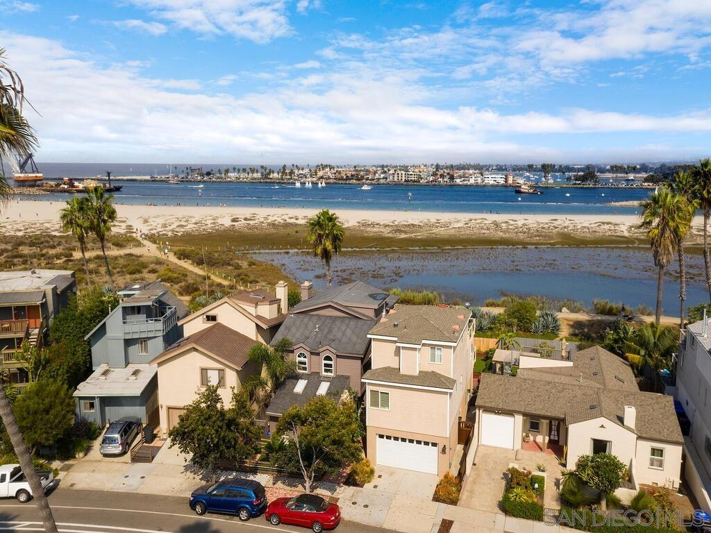 Treasure on the sand in OB!  Backs to Mission Bay channel, SD river, and dog beach. Step out to the sand and walk your dogs leash free. Stroll down to 3rd Corner & other OB attractions. Serene sit-down views to Sea World, Mission Bay & La Jolla from many rooms. Original owner. House built in '78 then expanded & remodeled in '03. Newly resurfaced decks off the 2nd & 3rd floors provide hrs of breathtaking views. Walk-out patio from ground floor 2nd en-suite master bedroom. Zoned for Hotel. Wonderland Beach.Granite kitchen counters, 4 burner Wolf stove, Bosch dishwasher, Samsung microwave and frig. The gorgeous stone-faced fireplace in LR is remote controlled and heats up the home in a snap with style & elegance. Top floor master bedroom also has its own view deck and remote controlled fireplace with a Fujitsu mini-split to heat & cool the 3rd floor.  A 2nd en-suite master bedroom can also be found on the entry level with private access to rear patio.  Wood plantation shutters & ceiling fans throughout, recessed lighting, tile bath & kitchen flooring, engineered oak flooring, two person marble walk-in shower, built in cabinets with rain glass in dining room.  All bedrooms have large walk-in closets with the 2nd floor bedroom currently being used as an office with built-in Murphy bed. Zoning is for hotel use.