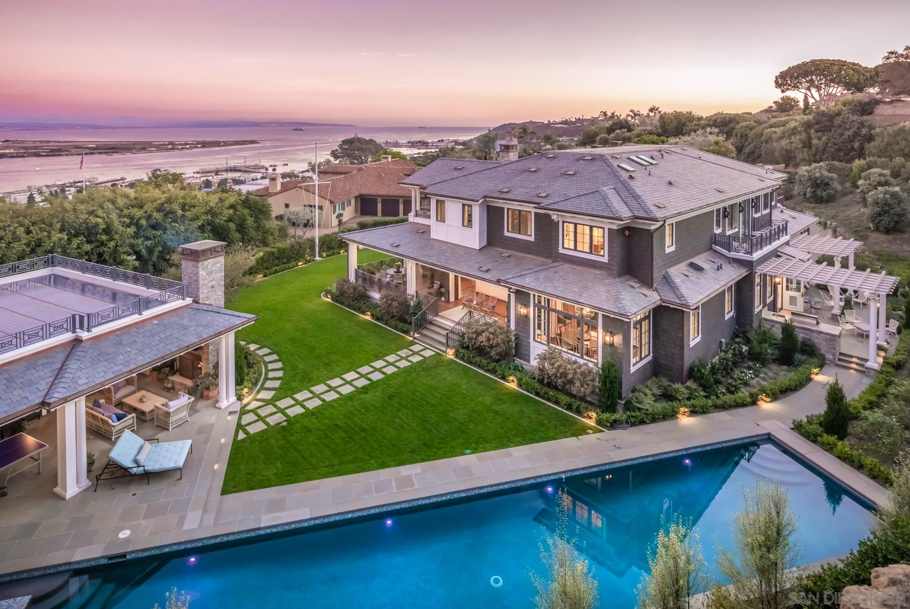 Entertaining offers b/w $13,500,000-$15,000,000. Luxury, private estate located within the exclusive, gated (12 home) community of La Playa in Point Loma. This Nantucket & Hamptons inspired home is situated on a rare almost 1 acre lot. Perfect to entertain with expansive wrap around porch complete with built-in ceiling heaters, multiple patios & decks, beautiful lawn, 75 foot lap pool & jacuzzi, 2 BBQ areas, 2 exterior wood burning fireplaces (4 interior gas fireplaces),3,000+ bottle wine cellar, detached guest house with gym & kitchenette & more. Other special amenities include private elevator, automated driveway gates & impressive 6+ car garage with turntable. This extraordinary estate was designed by Ione Stiegler & built by Steigerwald-Dougherty. The home features stunning walnut floors throughout, slate roof with copper gutters, solar, back-up generator, total home water filtration system, Lutron lighting system, Crestron total home entertainment system, cameras, security system, 2 exterior fountains, custom exterior light fixtures & more!  Impeccably designed, the home's main level offers 1 bedroom, an office, stunning kitchen with La Cornue double ovens, elegant dining room, 2 powder bathrooms featuring gorgeous marble throughout, chef's dream butler's pantry, mud room, living room with bar & family room with disappearing glass doors. The 2nd level offers the master retreat, 3 en-suite bedrooms + optional 4th bed/bath which is currently a movie theater. The detached guest house offers a gym, 2 full bathrooms, 1 bedroom & a kitchenette! Prepared to be amazed. Every detail from floor to ceiling will take your breath away!