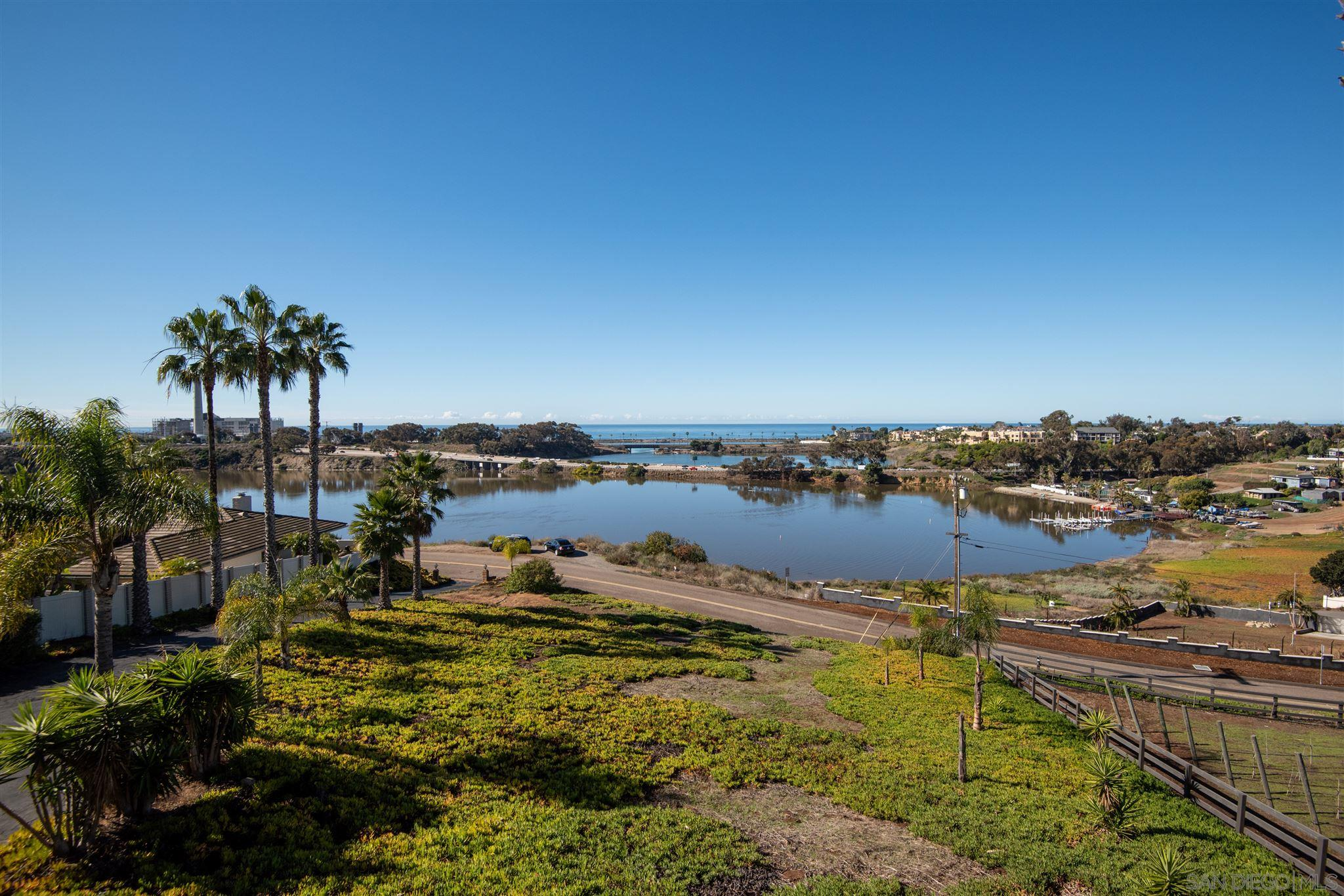 """W-O-W!!! You won't believe your eyes when you see this  enormous, 180 degree, uninterrupted ocean & lagoon view. This 27,007 SF lot is the last property before the lagoon, so there are no rooftops in your site - just the beautiful layers of the lagoon out to sweeping ocean & horizon panoramas - making it the ultimate view property. This hilltop property was handpicked by the owners 40+ years ago and offers a rare opportunity to remodel or build on one of the best sites in the area.Rich with warmth and character, this custom-built home has beautiful vaulted, wood beamed ceilings, 2 brick fireplaces, private master with west facing balcony, 2 guest suites on the main level plus a den/office/gym, detached oversized 2 car garage, & fenced backyard. Guests enter the home from the front door into the formal entry while family has easy access directly off the driveway into the kitchen. Bright and spacious, it opens to a large dining area and generous living room with picturesque windows providing ample light and fantastic scenery. A combination laundry/utility/mud room connects the kitchen to the fenced backyard and pedestrian door to the garage that can double as a workshop and has plenty of storage space. Designed for privacy, the second floor is set apart as the master suite and has a sitting area with fireplace, walk-in closet, makeup vanity, and a walk-out balcony with commanding views. The covered front porch is the perfect spot for admiring the sunsets and overlooks the grounds which are ripe with potential and would be ideal for a vineyard. A truly magical location and a once-in-a-lifetime opportunity for those looking for the ultimate in views and a home with """"excellent bones""""."""