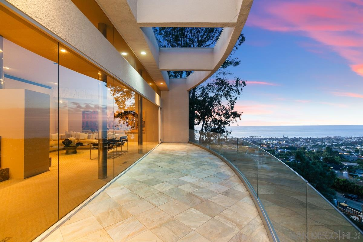 This beautiful contemporary home showcases walls of glass accentuating absolutely awe-inspiring views overlooking the city, golf course and ocean. An artfully designed pivot door and rounded travertine wall welcome you into the open interior featuring 4 bedrooms, 3.5 baths plus an office, generously-sized living and dining rooms separated by a dual-sided fireplace, and numerous skylights found throughout. The serene master suite, perfectly situated away from the 2 secondary bedrooms on the main floor…boasts a view deck, fireplace, abundant storage in its L-shaped display closet, and a spacious stone bath. An ideal space for older children or as a guest quarters, the lower level offers an en suite bedroom and large living area with a 2,200 bottle climate-controlled wine cellar. Peace and privacy abound from the lushly landscaped pool patio providing more than ample space for lounging, sunbathing or soaking in the elevated spa while enjoying the views. Sought-after Muirlands locale!