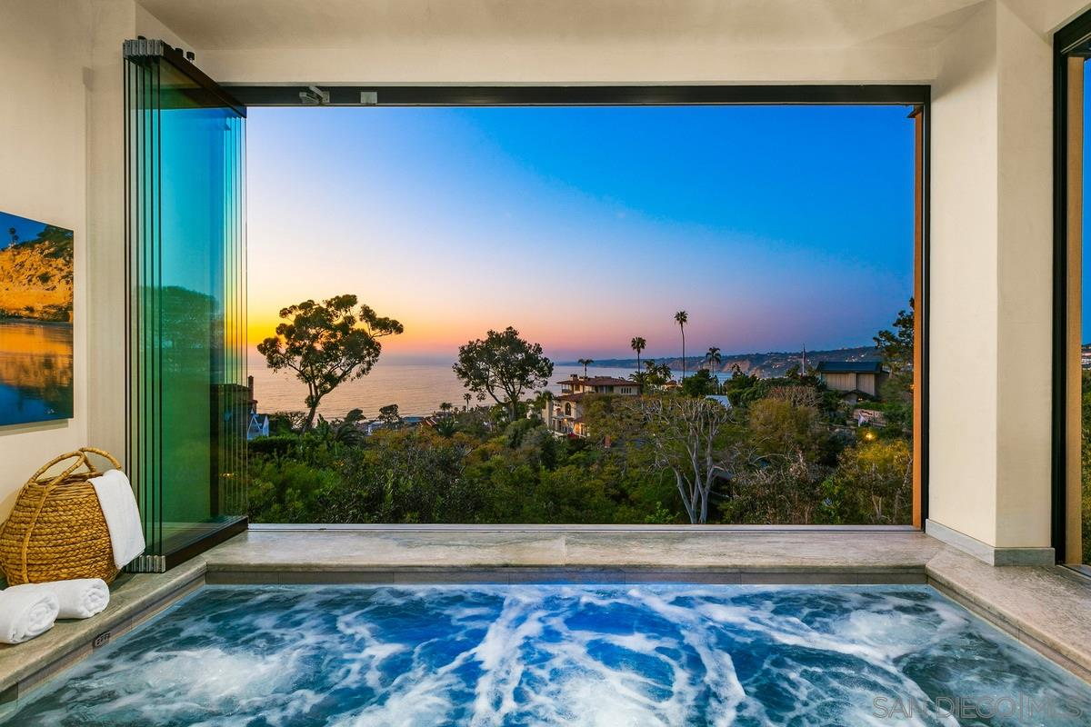 A truly special and distinctive trophy property, this Classic Beauty presents panoramic ocean views, abundant privacy and a prestigious Country Club locale. Set back from the street on a 0.61-acre parcel, the residence is positioned at the elevation of 210 feet above sea level atop a canyon which provides for spectacular North Shore white water views. An automatic entry gate slides back to reveal the home's architectural elegance and pristine grounds bordered by hedges. The unique floor plan offers dual master suites plus an office, 3 baths plus a powder room, and generous entertaining spaces with an inviting indoor-outdoor flow (continued).Inside, you're immediately greeted by gorgeous water views from almost every room. The formal living room features a fireplace, beautiful hardwood floors, and motorized pocket doors allowing a seamless transition onto an expansive outdoor living area with skylights and built-in heaters. Beyond, the meticulously landscaped backyard offers a putting green, built-in barbeque and a tranquil environment to enjoy the coastal scenery. The remodeled kitchen boasts an abundance of cabinetry, granite-topped counters & island, a breakfast area, and walk-in pantry. There are 2 sprawling master retreats, each with dual walk-in closets, spacious bathrooms, and breathtaking views. Additionally, the entry level master suite has its own sitting room, while the second master suite encompasses the entire 2nd floor. Spectacular sea views continue from the enclosed spa, providing seclusion and protection from the elements, or you can open the two walls of paneled glass to bring the outdoors in. With over 5,400 sq. ft. within the home, there is ample space to easily create additional bedrooms should that better suit your family's needs. Parking consists of garage spaces for 3 cars plus 6 designated spaces in the secure, semi-circular drive. Other notable items: a 2015 remodel including the kitchen, entry level master expansion and backyard, solar pane